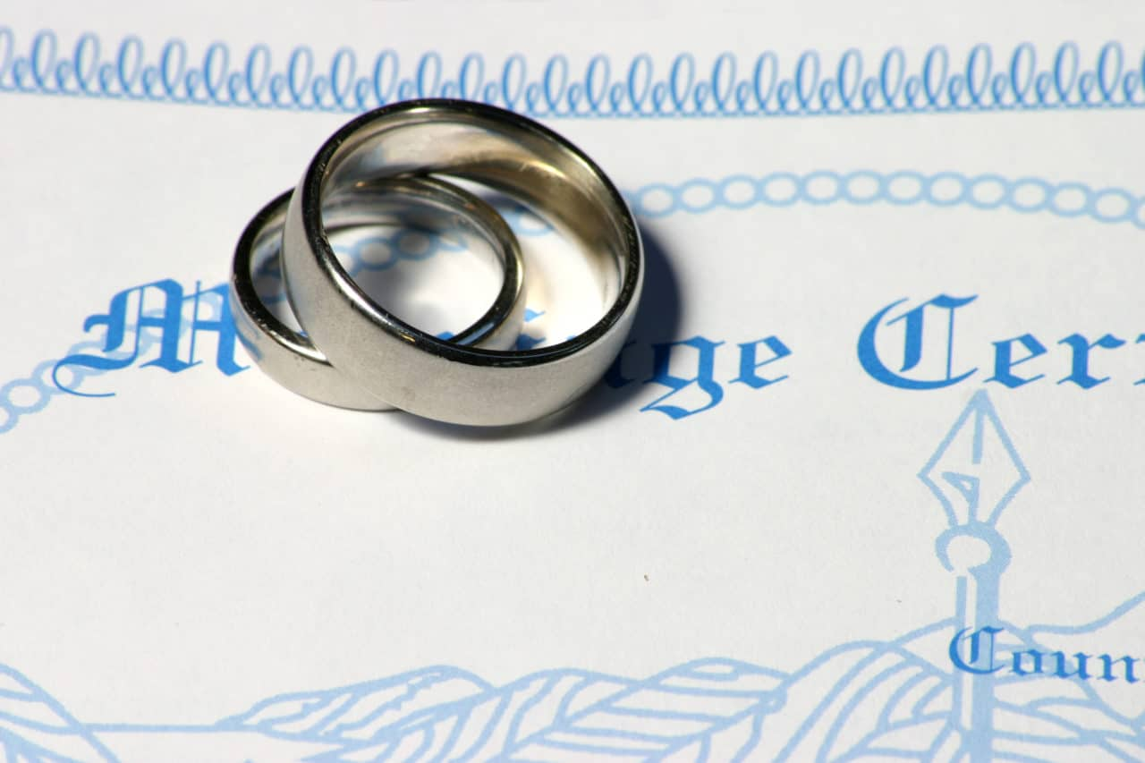 wedding bands in white-gold sitting on top of a marriage certificate