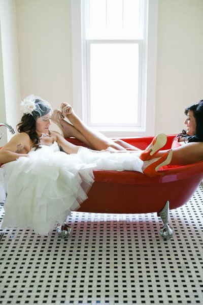 Bride and Maid of Honor chillen in the bathtub in their dresses