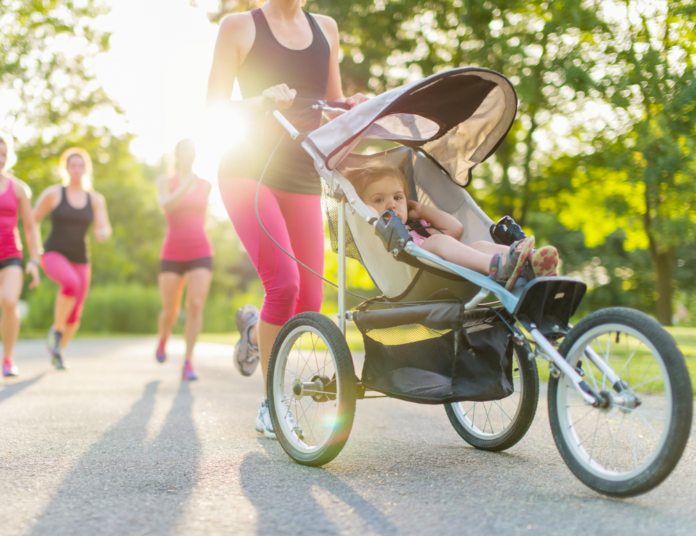 A woman pushing a stroller on her fitness routine