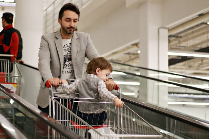 man pushing his son while sitting in a shopping cart