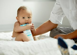 topless baby hugging white soft-tube