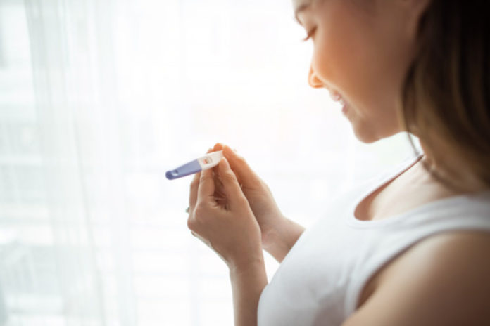 Woman smiling while holding pregnancy test